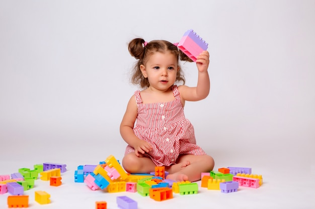 Baby girl playing with multicolored constructor
