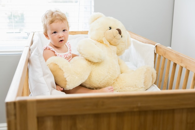 Baby girl playing with a teddy bear in a cradle