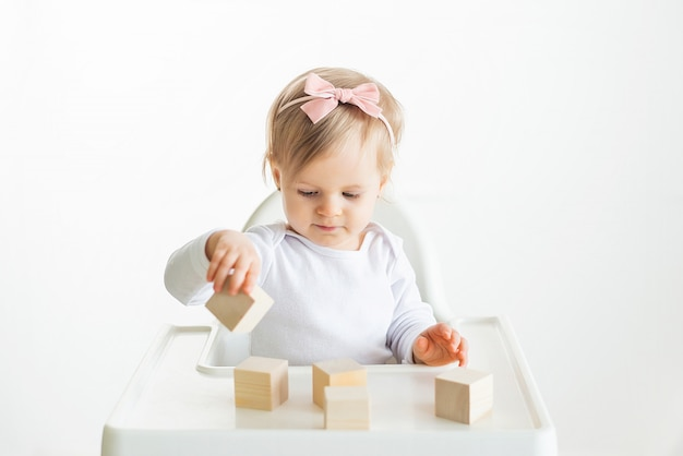 Baby girl playing with wooden cubes by left hand. playing toddler isolated on white background. games for kids, preschool education. close up, selective focus
