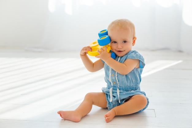 노란색 장난감 코끼리를 가지고 노는 아기 소녀. 웃 고 작은 아이