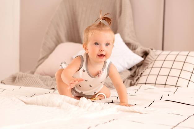Baby girl plays in a bedroom