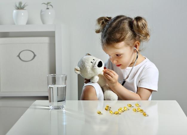 女の赤ちゃんは子供部屋で医者を演じて、きちんとしたクマに黄色いカプセルを与えます