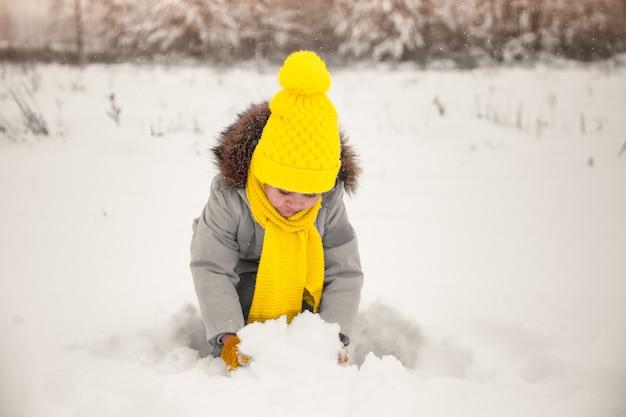 女の赤ちゃんは冬の自然の中で雪で遊ぶ。トレンディな色の服。