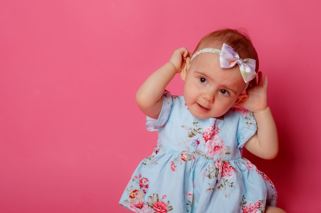 Baby girl portrait dressed in a dress sitting on a pink background