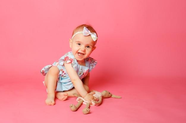 Портрет девочки, одетый в платье, сидя на розовом фоне