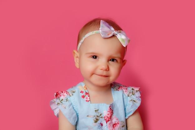 ピンクの上に座ってドレスを着た赤ちゃんの少女の肖像画