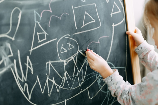 Baby girl pupil draws a funny monster with chalk on a black blackboard