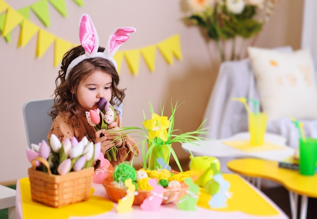 Baby girl in rabbit ears sitting at table. easter decor