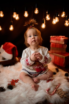 Baby girl in a red christmas costume with retro garlands sits on a fur