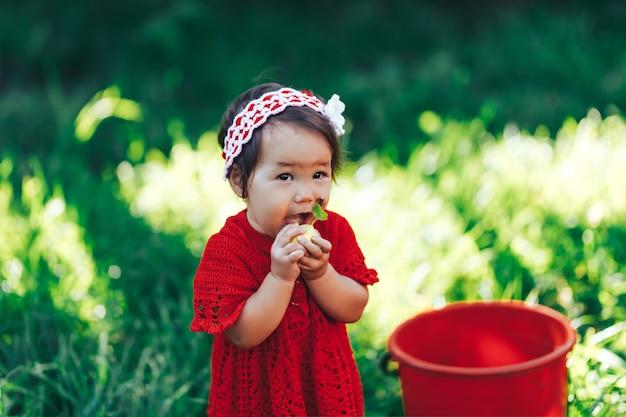 Baby girl in red dress eating pear in summer garden near red bucket