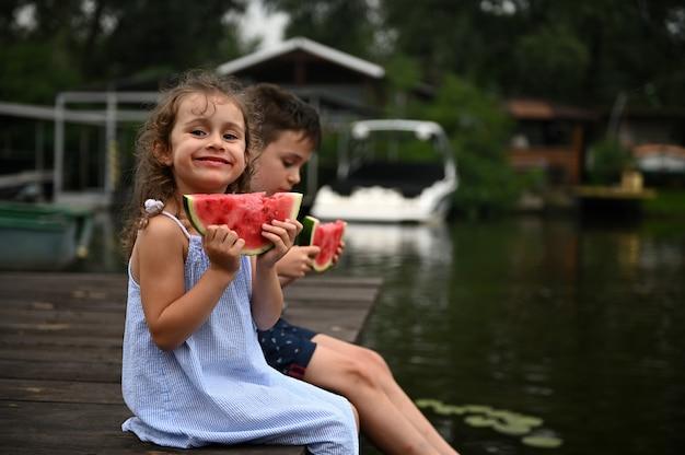 兄の隣の桟橋で休んでいる女の赤ちゃんがスイカを手に持って微笑む夏