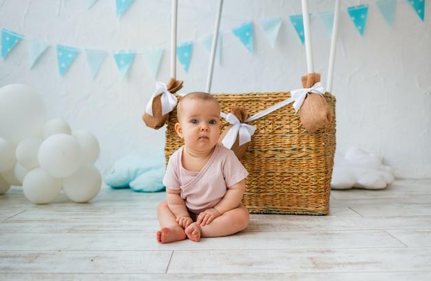 아기 소녀 풍선 바구니에 대 한 바닥에 앉아