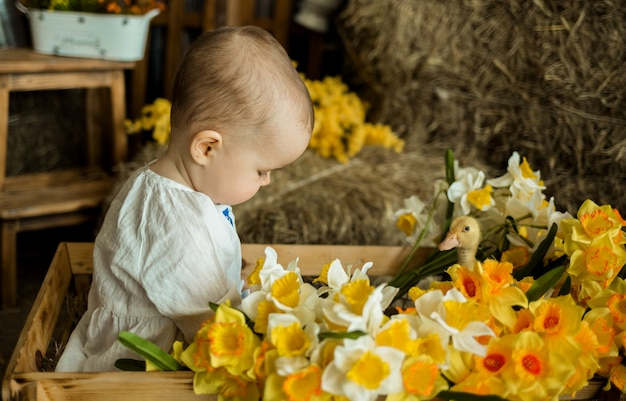 A baby girl sits in a wooden cart with yellow flowers and plays with a yellow duck