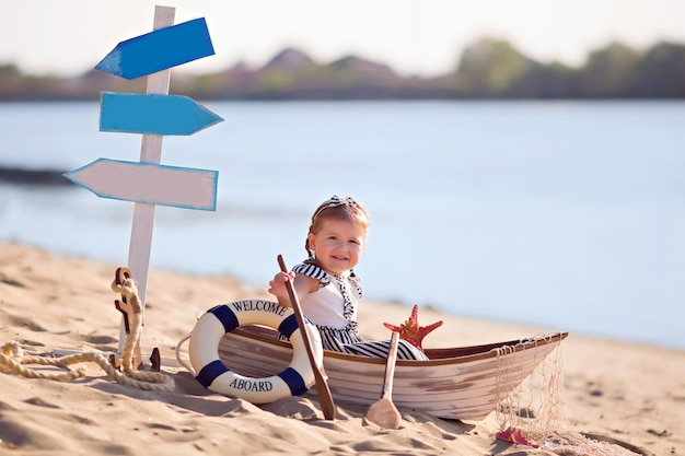Baby girl sitting in a boat, dressed as a sailor, on a sandy beach with seashells by the sea