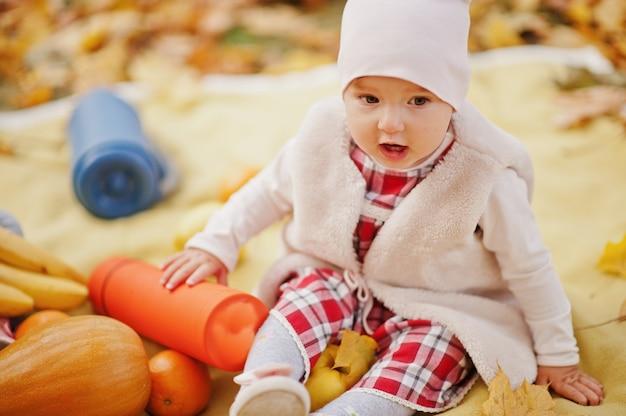 Baby girl sitting on carpet at autumn park.