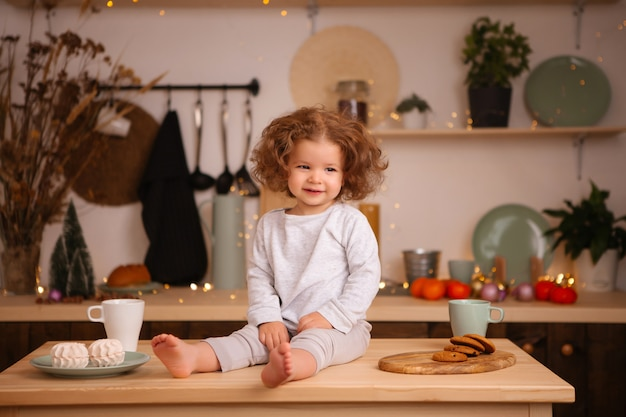 Baby girl sitting in christmas kitchen on table