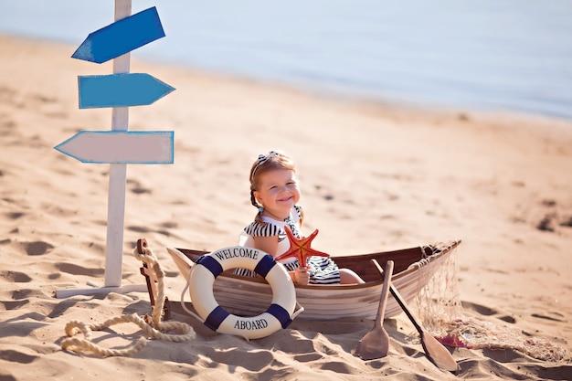 ビーチでボートに座っている女の赤ちゃん