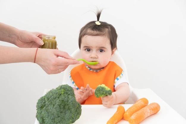 野菜のピューレを食べるチャイルズチェアに座っている女の赤ちゃん。ママは赤ちゃんを養います。