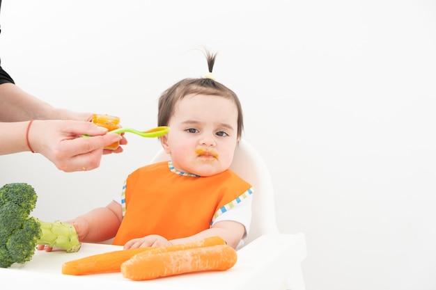 白で野菜のピューレを食べるチャイルズチェアに座っている女の赤ちゃん