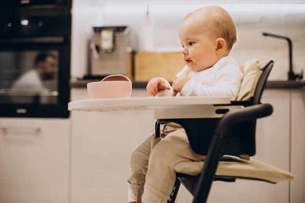 椅子に座ってお粥を食べる女の赤ちゃん