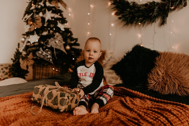 Девочка сидит в пижаме на кровати в спальне и открывает подарок. рождественское утро. новогодний интерьер. празднование дня святого валентина Premium Фотографии