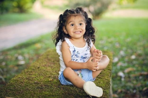 Девочка сидит на лугу, играя босой ногой, пытаясь нести ее ко рту.