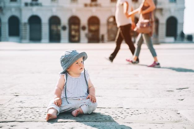 ヨーロッパの街の通りに座って、町の屋外で小さな子供を指さした女の赤ちゃん