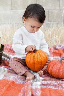 Девочка сидит на мягком одеяле и держит оранжевую тыкву на открытом воздухе