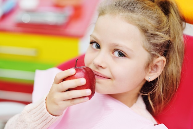 Baby girl sitting in a red dental chair smiling with a red apple in her hands. pediatric dentistry, milk teeth.