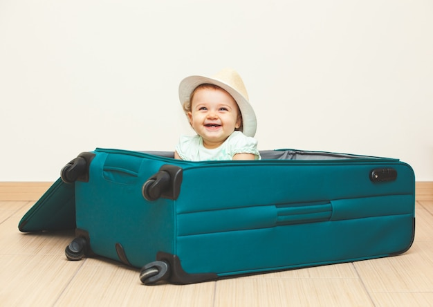 Baby girl sitting in suitcase on the floor with empty background.