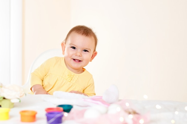 Baby girl sitting at the table and painting holiday easter eggs smiling happy childhood