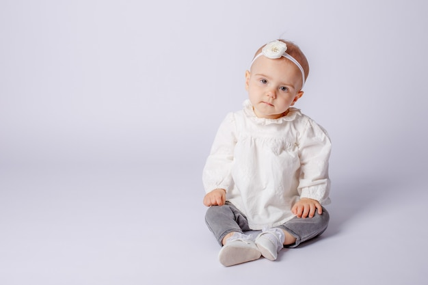 Baby girl sitting on a white background isolated