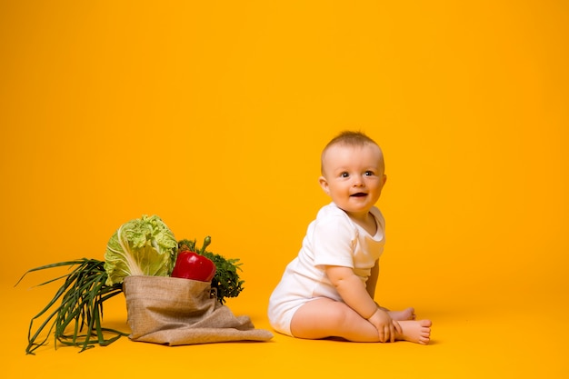 Baby girl sitting with bag of vegetables on yellow