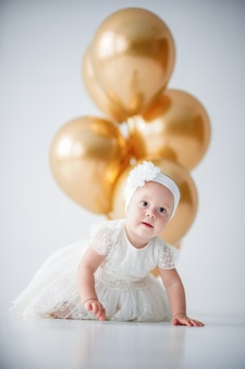 Baby girl sitting with a bunch of golden balloons