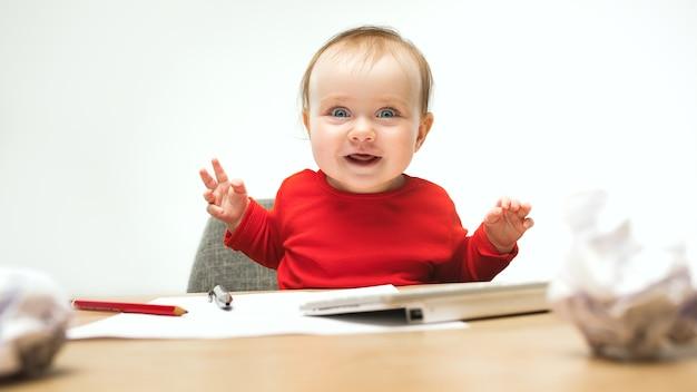 一杯のコーヒーとキーボードで座っている女の赤ちゃん