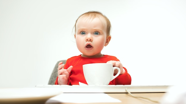 一杯のコーヒーと座っている女の赤ちゃん
