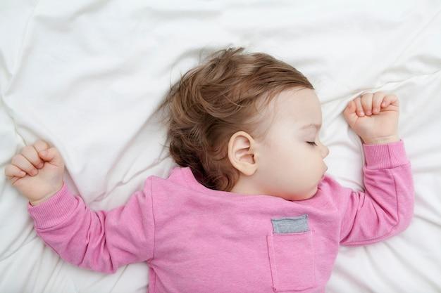Девочка спит на белой кровати, руки подняты вверх