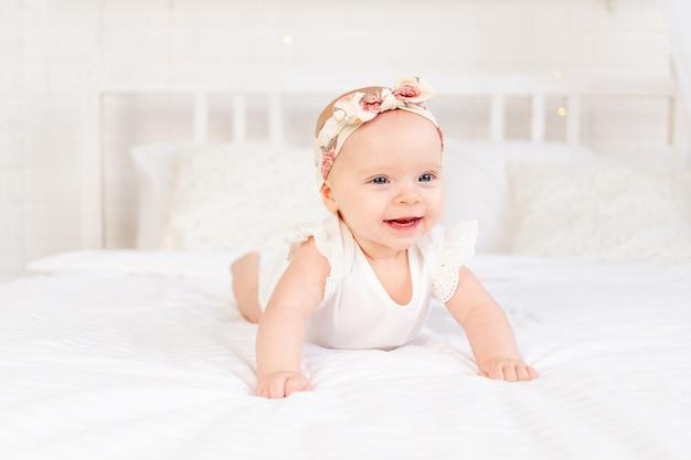 여자 아기는 집에 있는 흰색 면 침대에 엎드려서 미소를 짓고 있습니다.