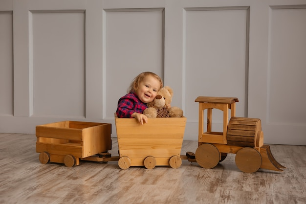 Ребёнок усмехаясь держащ плюшевого медвежонка, сидя в паровозе игрушки деревянном. место для текста
