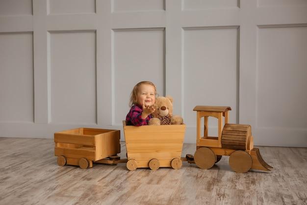 Девочка улыбается, держа плюшевого мишку, сидя в игрушечном деревянном паровозе
