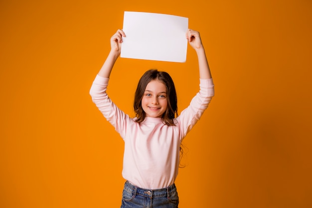 Baby girl smiling holding a blank sheet on a yellow background
