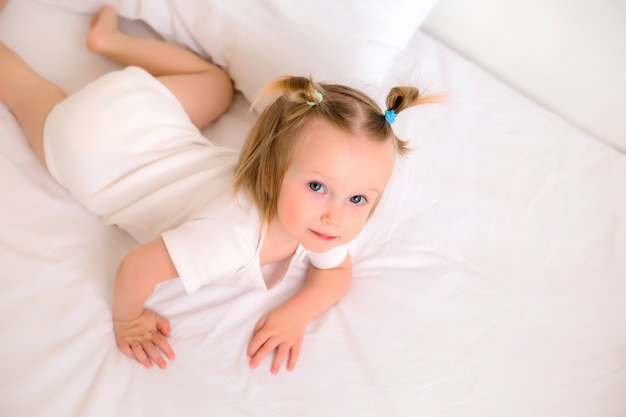 Девочка, улыбаясь в белой одежде, лежа на кровати с белым постельным бельем