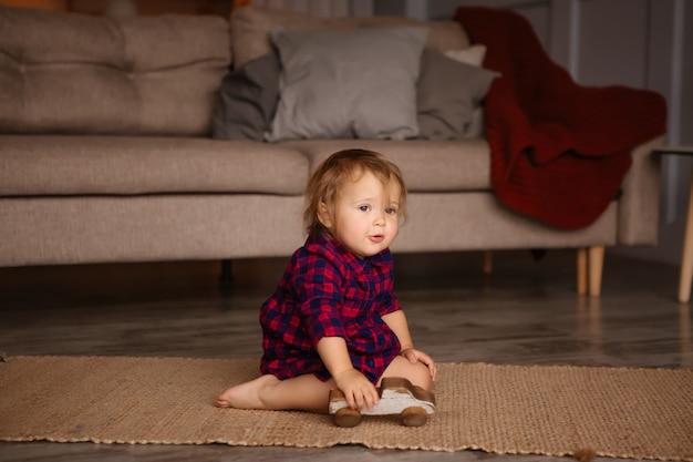 Девочка улыбается, играя на полу дома. остаться дома