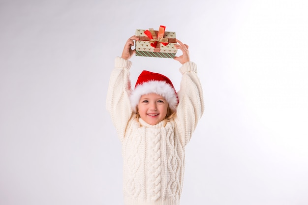 Baby girl smiling in santa hat holding gift box on white background