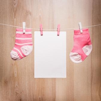 ロープと空白のカードに取り付けられた女の赤ちゃんの靴下