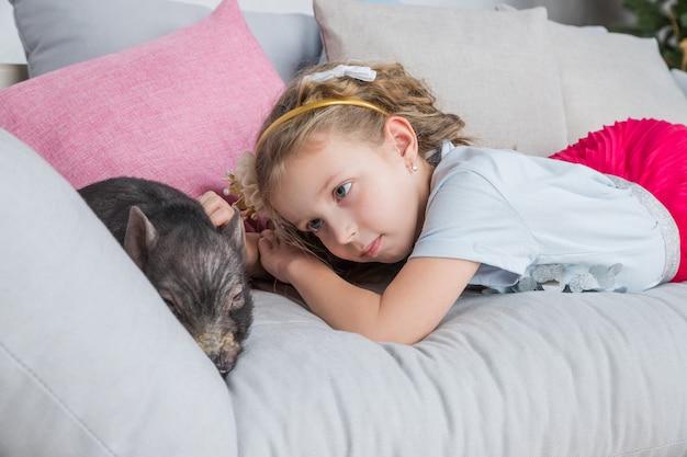 Baby girl on sofa near a black vietnamese piglet