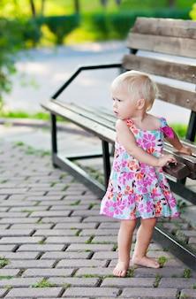 ベンチの近くに立っている女の赤ちゃん