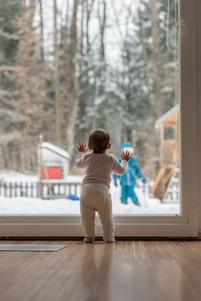 Baby girl standing at a window watching her brother outdoors playing in winter snow in the garden.