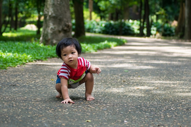 A baby girl start walking first on the park