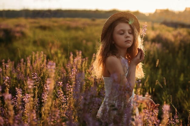 A baby girl in a straw hat stands in a field of flowers at sunset in summer